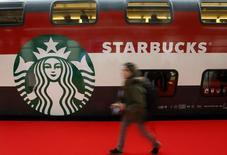 Женщина проходит мимо вагона с логотипом Starbucks на вокзале в Цюрихе 14 ноября 2013 года. Продажи Starbucks Corp в ключевом американском регионе во главе с США снизились в минувшем квартале сильнее, чем прогнозировали аналитики, так как большинство клиентов компании предпочли совершать покупки онлайн, сократив количество вылазок в кофейни. REUTERS/Arnd Wiegmann