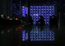 Pedestrians walk past an electronic board showing various stock prices, which are reflected in a polished stone surface, outside a brokerage in Tokyo January 24, 2014. REUTERS/Yuya Shino