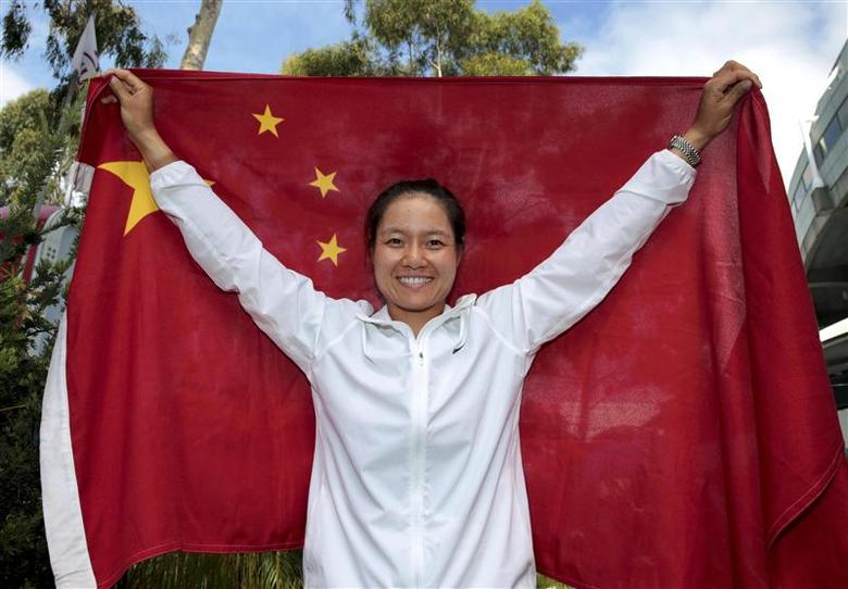 Li Na of China, finalist in the women's singles, poses with a Chinese national flag at the Australian Open 2014 tennis tournament in Melbourne January 24, 2014 in this handout image provided by Tennis Australia. REUTERS/Fiona Hamilton/Tennis Australia/Handout via Reuters