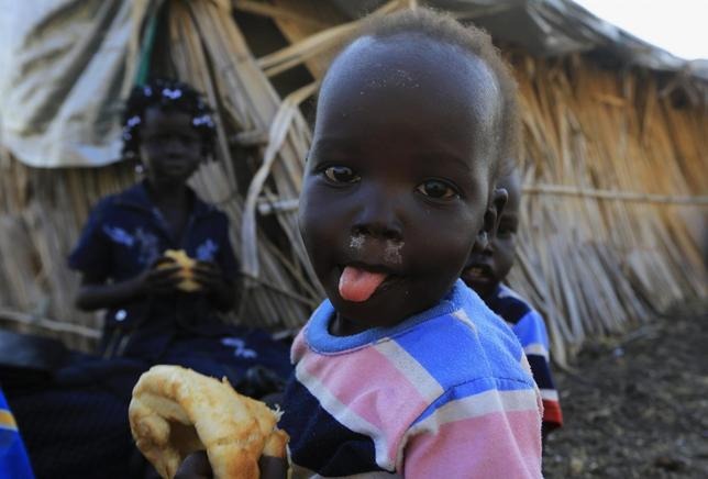 South Sudanese refugee children eat near a border gate in Joda, in the Jableen locality in Sudan's White Nile State, after arriving from the South Sudanese war zones of Malakal and al-Rank, January 16, 2014. REUTERS/Mohamed Nureldin Abdallah