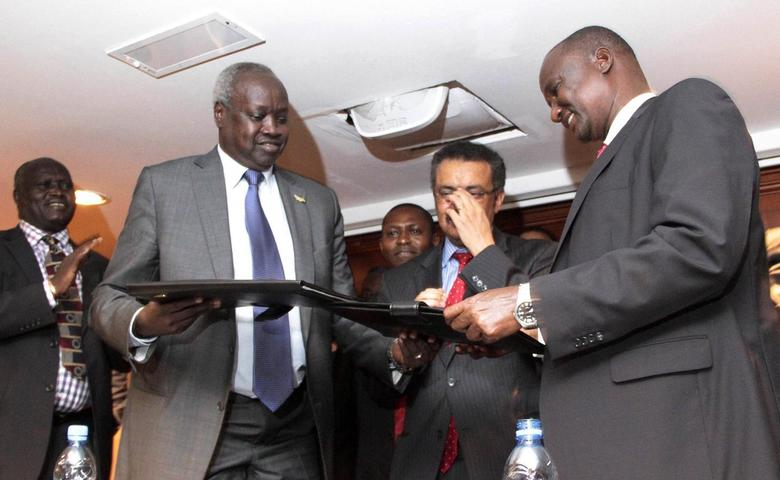 South Sudan's leader of the government's delegation Nhial Deng Nhial (L) exchanges a signed ceasefire agreement with the head of the rebel delegation General Taban Deng Gai (R) to end more than five weeks of fighting after negotiations in Ethiopia's capital Addis Ababa, January 23, 2014. REUTERS/Birahnu Sebsibe
