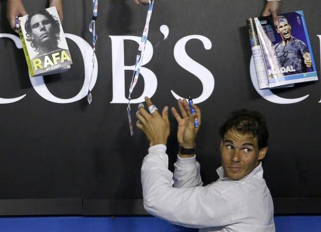 Rafael Nadal of Spain signs autographs after defeating Roger Federer of Switzerland in their men's singles semi-final match at the Australian Open 2014 tennis tournament in Melbourne January 24, 2014. REUTERS/Jason Reed