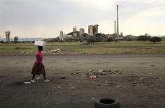 Una mujer pasa frente a una mina de Lonmin en el poblado de Ikaneng en Rustenburg, Sudáfrica, ene 24 2014. El mayor sindicato del sector de platino en Sudáfrica reanudará la próxima semana conversaciones auspiciadas por el Gobierno con las tres principales productoras mundiales del metal, en un intento por poner fin a una huelga por demandas salariales que empezó a tornarse violenta en su segundo día. REUTERS/Siphiwe Sibeko