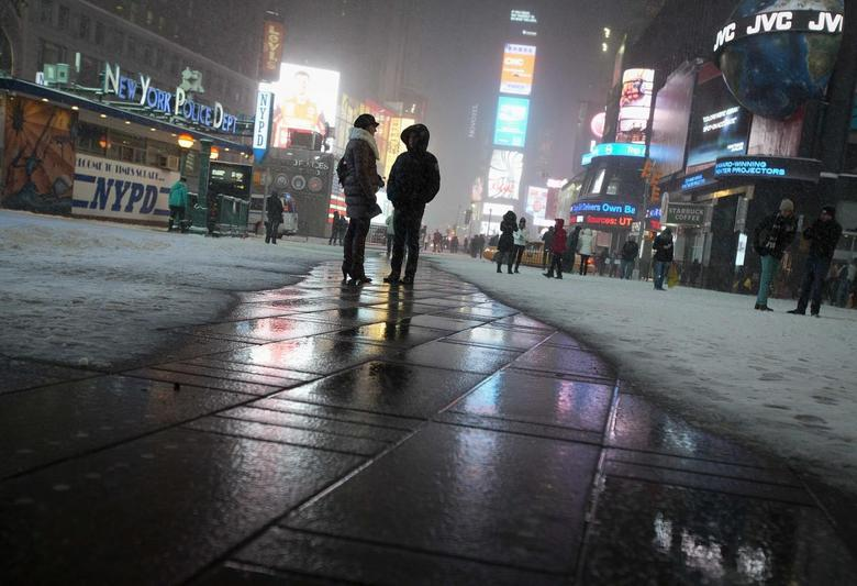 People stand on a heated section of pavement as it snows in Times Square in New York, January 3, 2014. REUTERS/Carlo Allegri