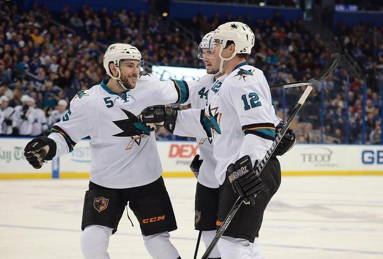 Jan 18, 2014; Tampa, FL, USA; San Jose Sharks defenseman Jason Demers (5), center Patrick Marleau (12) and defenseman Marc-Edouard Vlasic (44) celebrate a goal against the Tampa Bay Lightning at Tampa Bay Times Forum. Mandatory Credit: Jonathan Dyer-USA TODAY Sports