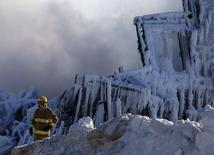 A firefighter looks on at the seniors residence Residence du Havre after a fire in L'Isle Verte, Quebec, January 23, 2014. REUTERS/Mathieu Belanger