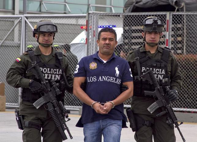 Colombian alleged drug trafficker Diego Perez Henao is escorted by policemen before being extradited from Bogota August 28, 2013. REUTERS/Inpec-Press Office/Handout via Reuters