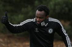Michael Essien of Chelsea gives a thumbs up as he arrives for a team training session at their training facility in Stoke D'Abernon, south of London, November 25, 2013. REUTERS/Andrew Winning