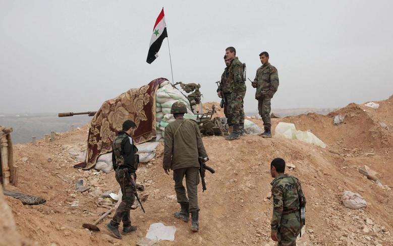 Syrian army soldiers loyal to Syria's President Bashar al-Assad stand in Talet Nabi Youssef in Aleppo Province, after claiming to have regained control of the town, January 23, 2014. REUTERS/George Ourfalian