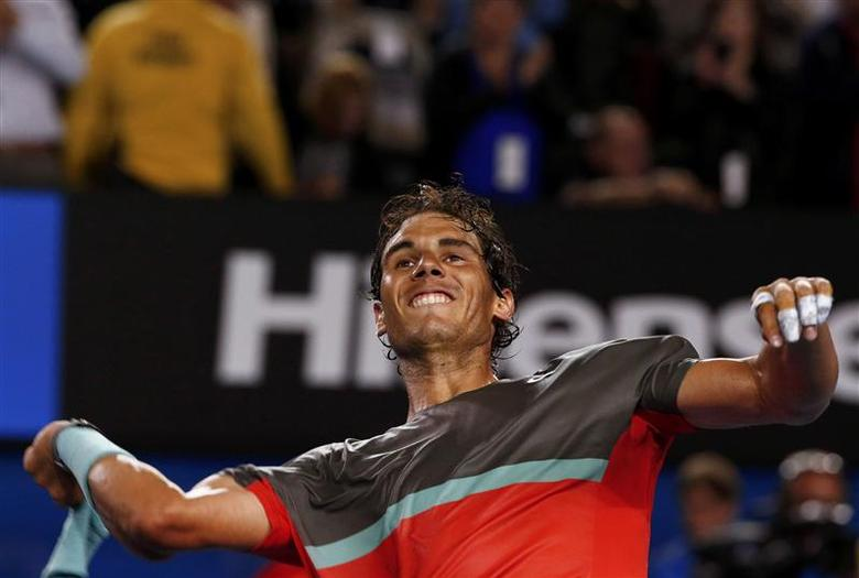 Rafael Nadal of Spain throws his sweatbands into the crowd as he celebrates defeating Roger Federer of Switzerland in their men's singles semi-final match at the Australian Open 2014 tennis tournament in Melbourne January 24, 2014. REUTERS/Petar Kujundzic