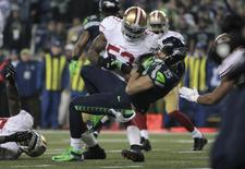 Seattle Seahawks Jermaine Kearse falls on the leg of San Francisco 49ers NaVorro Bowman injuring his knee as he loses control of the ball during the fourth quarter in the NFL's NFC Championship football game in Seattle, January 19, 2014. REUTERS/David Ryder
