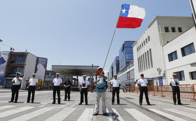 A Chilean dock worker waves a Chilean flag at a rally against the government at the entrance of the port during a strike in Valparaiso city, about 121 km (75 miles) northwest of Santiago, January 16, 2014. REUTERS/Eliseo Fernandez