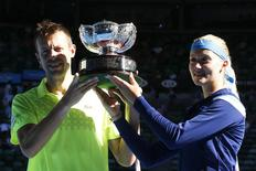 Kristina Mladenovic of France and Daniel Nestor of Canada pose with the trophy after defeating Horia Tecau of Romania and Sania Mirza of India in their Mixed Doubles final match at the Australian Open 2014 tennis tournament in Melbourne January 26, 2014. REUTERS/Bobby Yip