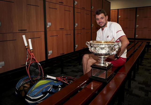 Stanislas Wawrinka of Switzerland sits with the Norman Brookes Challenge Cup in the locker room after defeating Rafael Nadal of Spain in their men's singles final match at the Australian Open 2014 tennis tournament in Melbourne January 26, 2014. REUTERS/Fiona Hamilton/Tennis Australia/Handout