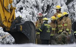 Emergency workers look on while digging through the remains of the senior residence Residence du Havre in L'Isle Verte, Quebec, January 25, 2014. REUTERS/Mathieu Belanger