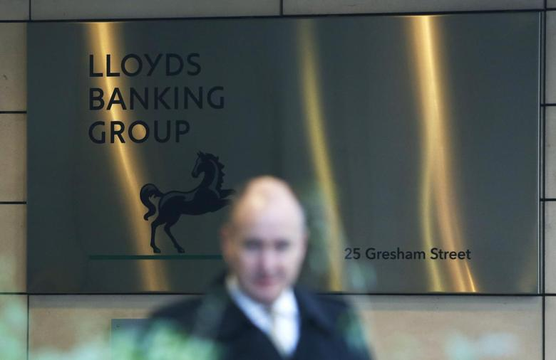 A man walks past the entrance to the head office of Lloyds Banking Group in the City of London December 11, 2013. REUTERS/Olivia Harris