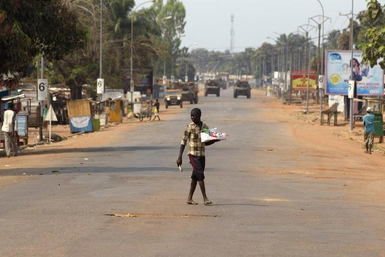 A street vendor crosses a largely empty road in Miskine district, Bangui January 25, 2014. REUTERS/Siegfried Modola