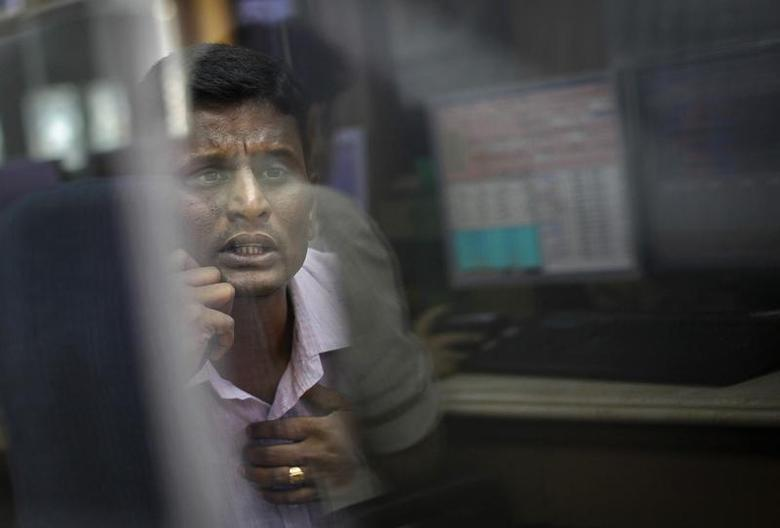 A broker looks at a computer screen as he talks on a phone at a stock brokerage firm in Mumbai December 3, 2012. REUTERS/Danish Siddiqui/Files