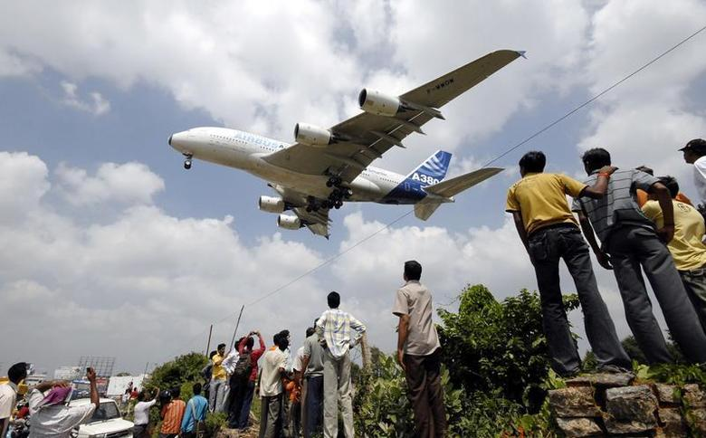 People look at an Airbus A380, the world's largest passenger aircraft, as it lands during India's first civil aviation exhibition and conference, ''India Aviation 2008'', in the southern Indian city of Hyderabad October 16, 2008. REUTERS/Krishnendu Halder