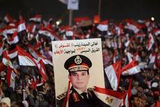 Сторонники командующего армией Абделя Фаттаха ас-Сиси держат плакат с его изображением на площади Тахрир в Каире 25 января 2014 года. Временный лидер Египта пересмотрел план возврата власти народу после военного переворота и решил провести президентские выборы до парламентских, что открывает дорогу к руководству государством сверхпопулярному командующему армией Абдель Фаттаху ас-Сиси, от которого ждут стабилизации политической ситуации в стране. REUTERS/Mohamed Abd El Ghany