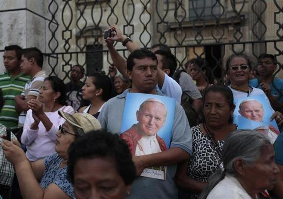 A man holds a poster with the image of Pope John Paul II during an annual procession for the Virgen De la Asuncion (Assumption Virgin) on the streets of downtown Guatemala City, August 15, 2013. REUTERS/Jorge Dan Lopez/Files