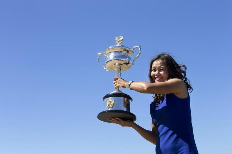 Li Na of China poses with the Daphne Akhurst Memorial Cup she won in the women's singles final match at the Australian Open 2014 tennis tournament during a photo call at Brighton Beach in Melbourne, January 26, 2014. REUTERS/Jason Reed