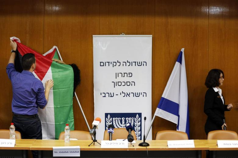 Israeli parliament employees set up a Palestinian flag (L) next to an Israeli one as they prepare ahead of a meeting between Israeli parliament members and a delegation of Palestinian politicians and businessmen, aimed at encouraging Israeli-Palestinian negotiations, at the Knesset, the Israeli parliament, in Jerusalem July 31, 2013. REUTERS/Baz Ratner