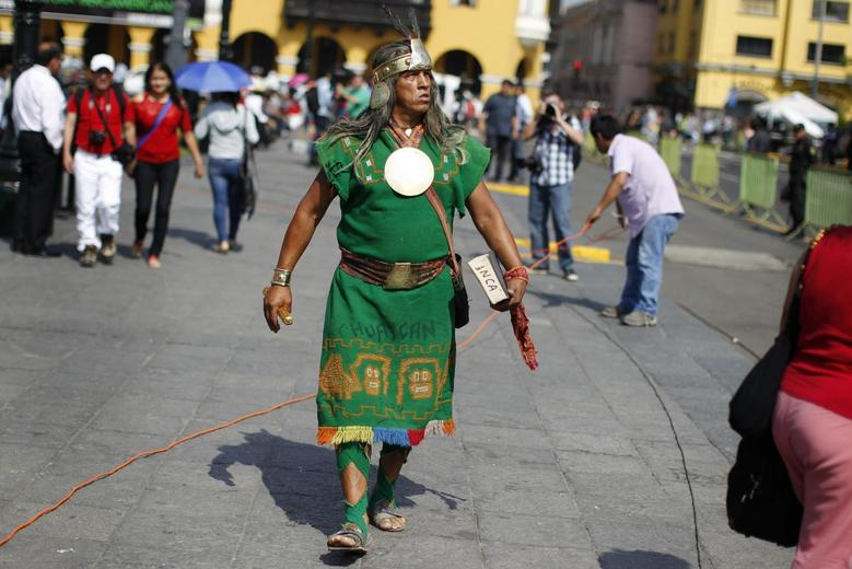A man dressed as a native Inca walks as he watches the final ruling court session of a decades-old maritime dispute between Peru and Chile, on a television screen in the yard of the Government Palace in Lima January 27, 2014. REUTERS/Enrique Castro-Mendivil