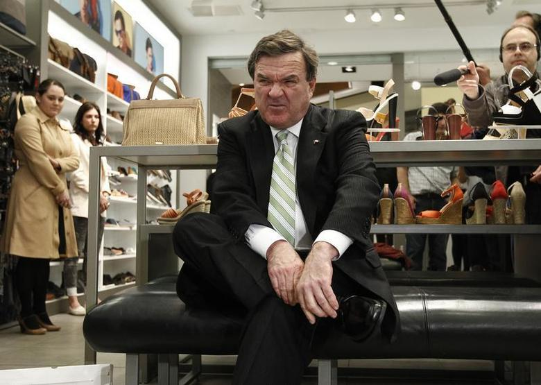 Canada's Finance Minister Jim Flaherty reacts while trying on his ''budget shoes'' during a photo opportunity at a shoe store in Ottawa March 28, 2012. REUTERS/Chris Wattie