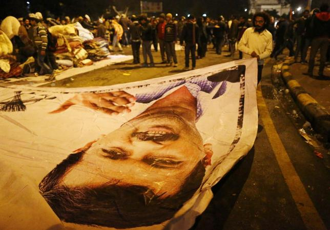 A supporter of Aam Aadmi (Common Man) Party (AAP) removes a poster with a portrait of Delhi chief minister Arvind Kejriwal from the site of a protest after Kejriwal called off the sit-in protest against the police in New Delhi January 21, 2014. REUTERS/Anindito Mukherjee