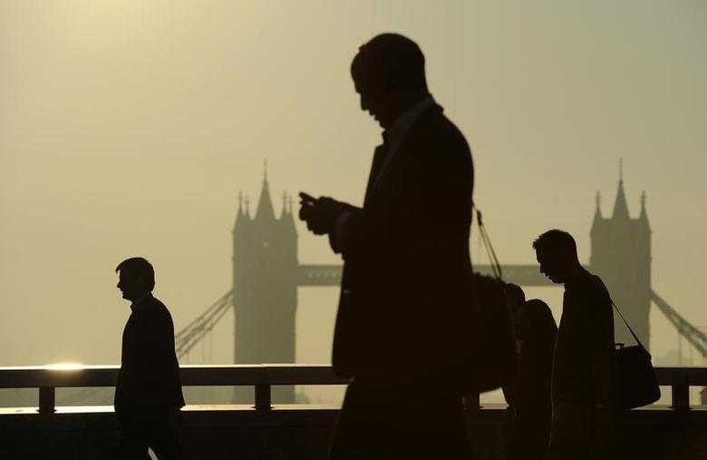 Workers cross London Bridge, with Tower Bridge seen behind, during the morning rush hour in London September 30, 2011. REUTERS/Paul Hackett/Files