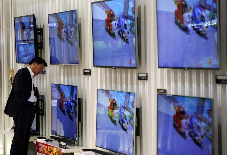 A customer looks at LG Electronics' TV sets which are made with LG Display flat screens at its store in Seoul January 23, 2014. REUTERS/Kim Hong-Ji