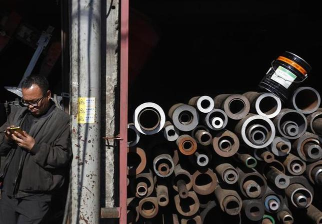 A worker uses his mobile phone during a break at a steel works in Seoul October 23, 2012. REUTERS/Kim Hong-Ji/Files