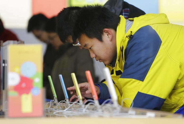 A customer tests an iPhone 5C at an Apple store in Beijing January 17, 2014. REUTERS/Jason Lee