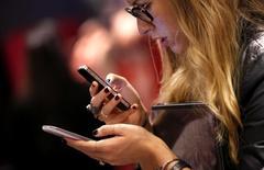 Женщина с двумя телефонами в Нью-Йорке 6 ноября 2013 года. Поставки смартфонов по всему миру впервые достигли отметки в один миллиард штук в 2013 году, подскочив на 38,4 процента, сообщила исследовательская фирма IDC. REUTERS/Mike Segar