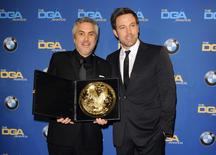 "Actor and director Ben Affleck (R) presents Mexican director Alfonso Cuaron with the Feature Film award for ""Gravity"" during the 66th annual Directors Guild of America Awards in Beverly Hills, California January 25, 2014. REUTERS/Gus Ruelas"