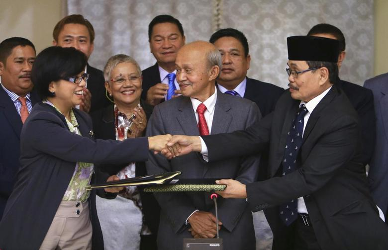 Government of the Philippines (GPH) chief negotiator Miriam Coronel Ferer shake hands with Moro Islamic Liberation Front (MILF) chief negotiator Mohagher Iqbal (R) as they exchange peace agreements between both parties at the GPH-MILF Formal Exploratory Talk in Kuala Lumpur January 25, 2014. REUTERS/Samsul Said