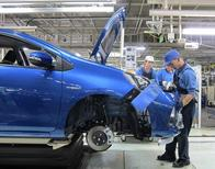 An assembly line worker attaches the bumper onto the body of a Toyota Aqua, the world's cheapest and most fuel-efficient conventional hybrid car, at a factory of the automaker's subsidiary, Kanto Auto Works, in Kanegasaki, Iwate prefecture, north of Japan in this March 9, 2012 file photo. Toyota Motor Corp plans to curb daily vehicle output in Japan by 15 percent in April from a year earlier as it adjusts for a dampening of demand from a national sales tax rise, a source familiar with its production plans said on January 28, 2014. REUTERS/Chang-Ran Kim/Files