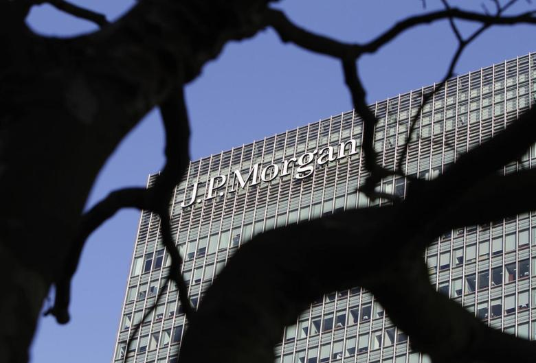 A sign on the Canary Wharf offices of JP Morgan is seen through the branches of a tree in London January 28, 2014. Police said they are investigating the ''non-suspicious'' death of a man who fell onto a ninth floor roof at the European headquarters of investment bank JP Morgan in London's Canary Wharf on Tuesday morning. REUTERS/Simon Newman