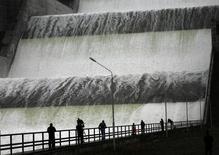 Журналисты фотографируют водосброс на Саяно-Шушенской ГЭС 12 октября 2011 года. Крупнейшая в РФ гидрогенерирующая госкомпания Русгидро увеличила производство электроэнергии в прошлом году на 10,4 процента до исторического максимума благодаря высокому уровню воды, сообщила компания. REUTERS/Ilya Naymushin