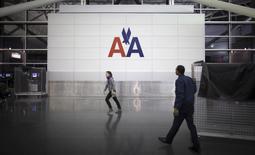 Pessoas caminham em frente ao logotipo da American Airlines no saguão do aeroporto internacional John F. Kennedy, em Nova York. A American Airlines, a maior companhia aérea do mundo após a fusão no ano passado com a US Airways, registrou prejuízo de 2 bilhões de dólares, ou 8,66 dólares por ação, no quarto trimestre, após encargos ligados à sua reorganização. 27/11/2013. REUTERS/Carlo Allegri