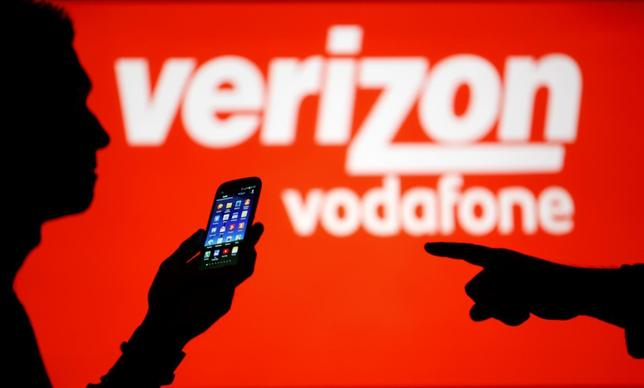 A man is silhouetted against a video screen with Vodafone and Verizon texts as he poses with a Samsung Galaxy S3 in this photo illustration taken in the central Bosnian town of Zenica, September 3, 2013. Picture taken September 3. REUTERS/Dado Ruvic