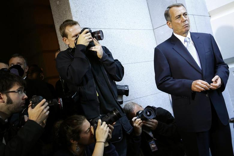 Photographers take pictures of U.S. House Speaker John Boehner (R-OH) (R) as he appears before reporters after a Republican caucus meeting at the U.S. Capitol in Washington, October 15, 2013. REUTERS/Jonathan Ernst