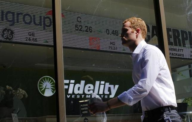 A pedestrian walks past a stock ticker at a Fidelity Investments office in Boston, Massachusetts July 31, 2013. REUTERS/Brian Snyder/Files