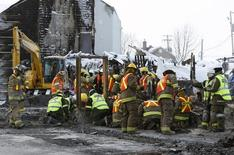 Emergency workers dig through the remains at the site of the Residence du Havre in L'Isle Verte, Quebec, January 28, 2014. REUTERS/Mathieu Belanger