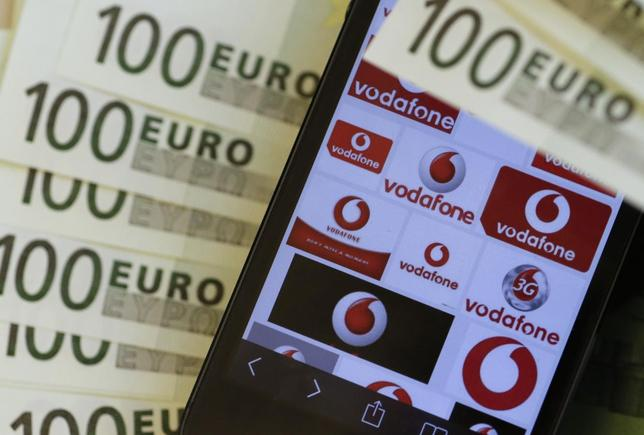 A photo illustration shows the company logo of mobile phone provider Vodafone and some 100 Euro bank notes in Vienna January 16, 2014. REUTERS/Leonhard Foeger