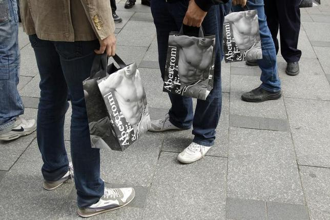 Shoppers hold bags with clothing purchases on the opening day of operations by retailers Abercrombie & Fitch outside their Paris store on the Champs Elysees May 19, 2011. REUTERS/Benoit Tessier
