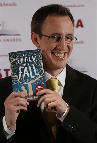 Nathan Filer poses for a photograph with his book ''The shock of the Fall'' in London January 28, 2014. REUTERS/Luke MacGregor