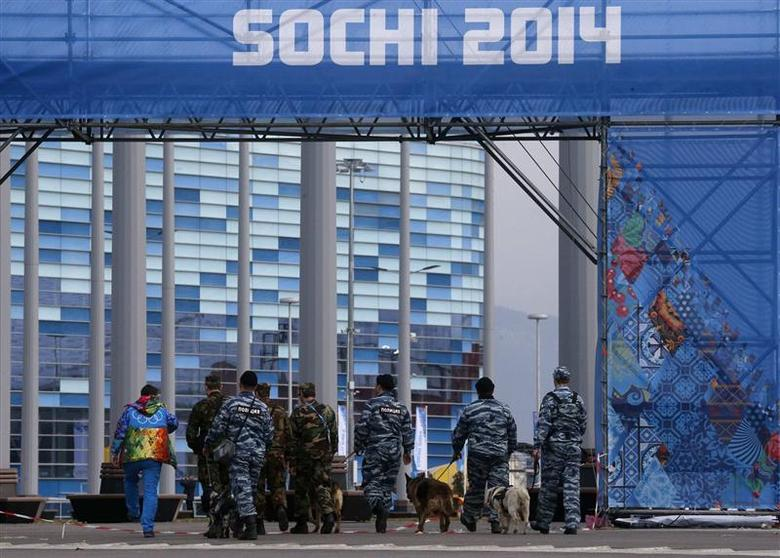 Police officers walk with sniffer dogs trained to search for explosives, as they patrol at the Olympic Park in the Adler district of Sochi, January 28, 2014. REUTERS/Alexander Demianchuk