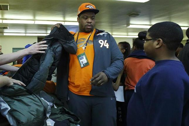 Denver Broncos defensive tackle Terrance Knighton (L) helps a kid to try on a jacket as part of an activity with The Knights of Columbus called ''Coats for Kids'' in Jersey City, New Jersey, January 28, 2014. REUTERS/Eduardo Munoz